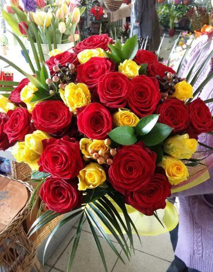 Buchet trandafiri rosii si galbeni pe rotund cu ruscus